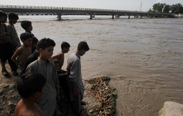 Na snímke ľudia stoja na beru rozvodnenej rieky Kábul v pakistanskom Pešaváre