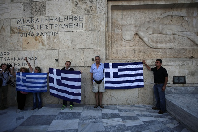 Grécki demonštranti proti úsporným opatreniam držia grécke zástavy