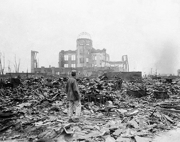 Na archívnej snímke z 8. septembra 1945 korešpodent stojí v ruinách pred budovou, ktorá je dnes známa ako Dóm atómovej bomby, mesiac po zhodení atómovej bomby na Hirošimu.