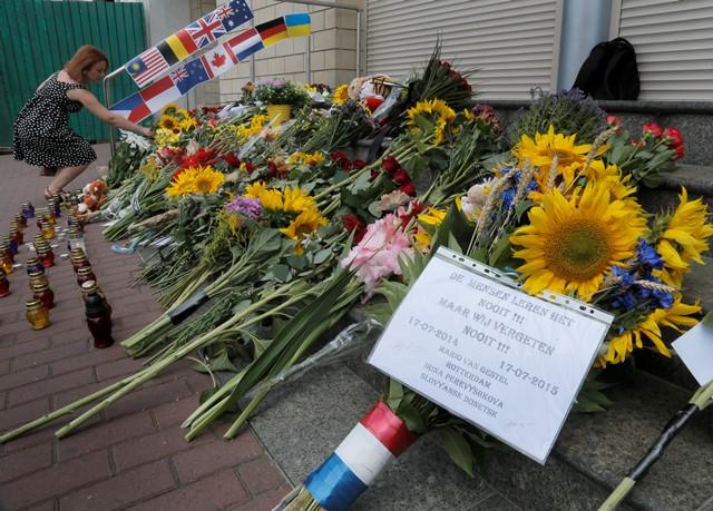 Na snímke ľudia kladú kvety  pred holandským veľvyslanectvom v Kyjeve 17. júla 2015 na pamiatku obetí pri príležitosti prvého výročia tragického zostrelenia malajzijského letu MH17 nad Ukrajinou