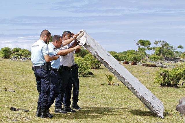 Na archívnej snímke z 29. júla 2015 francúzski policajti kontrolujú časť lietadla v meste Saint-André na severovýchode ostrova Réunion patriaceho k Francúzsku.