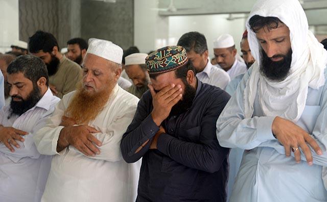 Pakistanci sa modlia za vodcu afganského Talibanu Muhammada Umara po oznámení o jeho úmrtí.