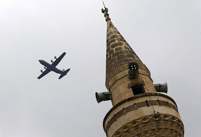 Transportné lietadlo amerického letectva C-130 Hercules za vežou mešity po štarte z leteckej základne Incirlik neďaleko tureckého mesta Adana v juhovýchodnom Turecku.