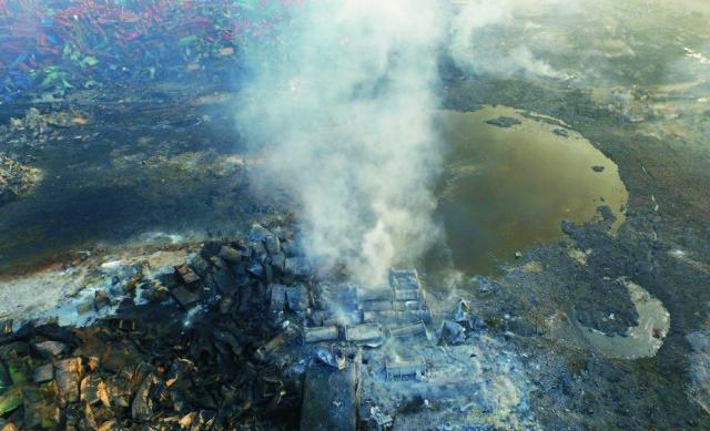 Na leteckej snímke stúpa dym z trosiek kontajnerov pri kráteri v epicentre série zničujúcich výbuchov v čínskom prístave Tchien-ťin 15. augusta 2015.  Mohutné výbuchy horľavých látok otriasli v stredu 12. augusta 2015 večer miestneho času priemyselnou časťou čínskeho prístavného mesta Tchien-ťin
