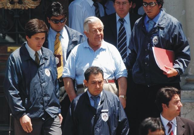 Na archívnej snímke z 28. januára 2005 Manuel Contreras (uprostred) odchádza zo sídla polície v Santiagu. Bývalý šéf obávanej tajnej služby v Čile, bol zodpovedný za únosy, mučenie a zavraždenie tisícov ľudí počas čilskej vojenskej diktatúry