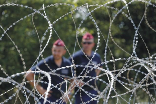 Maďarskí policajti hliadkujú za ostnatým drôtom na plote počas výstavby dočasných zábran na maďarsko-srbských hraniciach pri juhomaďarskej obci Mórahalom, 179 km juhovýchodne od Budapešti