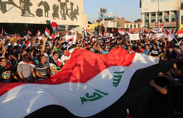 Na snímke ľudia mávajú národnou vlajkou počas demonštrácie v Bagdade