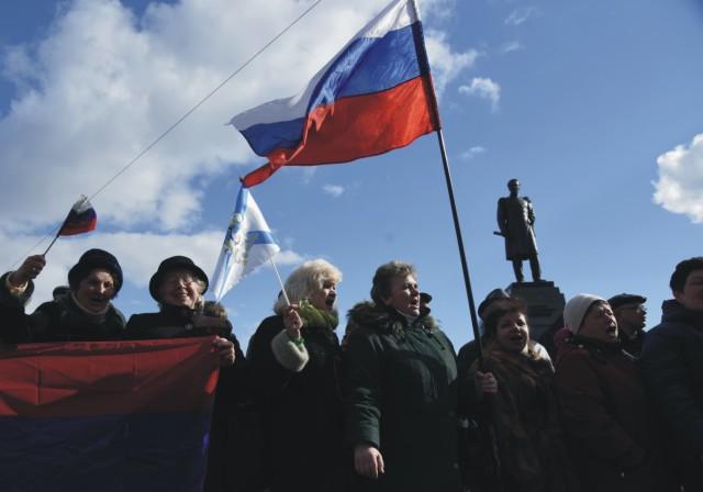Na archívnej snímke miestni obyvatelia mávajú ruskými vlajkami počas vojenskej prehliadky v meste Sevastopoľ
