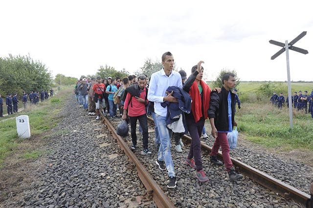 Migranti, ktorí sa rozhodli opustiť záchytný tábor pre utečencov, kráčajú pešo popri železničnej trati v meste Röszke na juhu Maďarska, na maďarsko-srbských hraniciach.