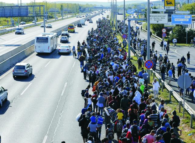 Na archívnej snímke skupina migrantov ktorá kráčala von z Budapešti 4. septembra 2015 po tom, ako sa rozhodli ísť pešo do Rakúska. Stovky migrantov sa vydali pešo z budapeštianskej Východnej železničnej stanice s vyhlásením, že smerujú do Rakúska. Migranti vyrazili pešo z hlavnej železničnej stanice v Budapešti po tom, ako sa nemohli dostať na vlaky k rakúskej hranici. Maďarsko vo štvrtok zrušilo všetky vlaky do západnej Európy
