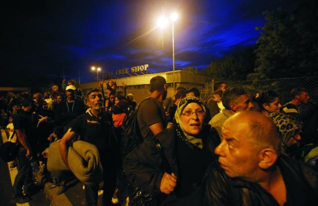 Migranti čakajú na prekročenie hraničného priechodu Horgoš 2 do Maďarska neďaleko srbskej obce Horgoš 14. septembra 2015