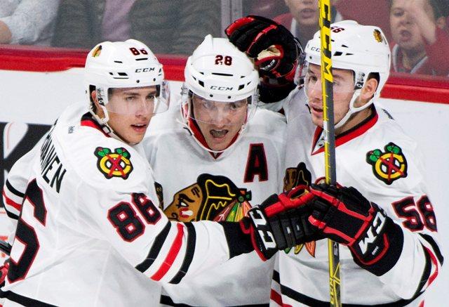 Na snímke hráči Chicaga Blackhawks Ryan Garbutt (uprostred) so spoluhráčmi Teuvom Teravainenom  (vľavo) a Markom Daňom