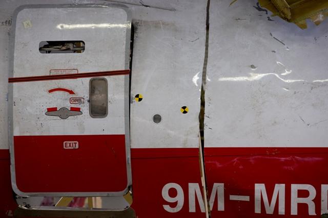 Na snímke registračné číslo lietadla na väčšom kuse trosiek lietadla Boeing 777 letu MH 17 Malazijskych Aerolínii nainštalovaný na stojanoch v hangári na leteckej základni Gilze Rijen v Holandsku