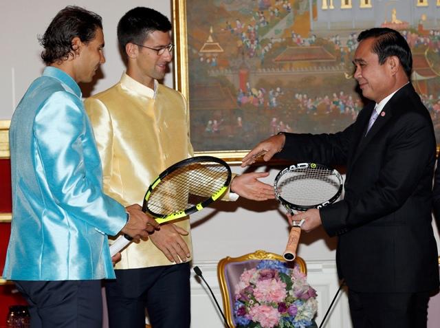 Na snímke srbský tenista Novak Djokovič (uprostred), španielsky tenista Rafael Nadal (vľavo) odovzdávajú tenisové rakety ako dar thajskému premiérovi Prajutovi Čan-o-Čanovi