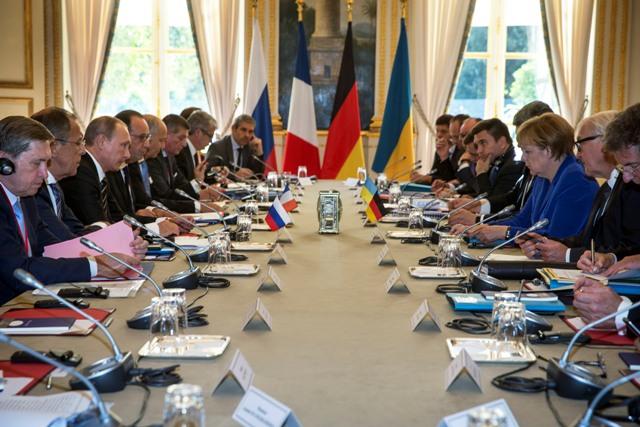 Nemecká kancelárka Angela Merkelová (tretia zľava), ruský prezident Vladimir Putin (tretí sprava) a francúzsky prezident Francois Hollande (štvrtý sprava) počas  rokovania  v Elyzejskom paláci v Paríži