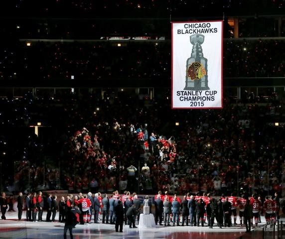 Na snímke obhajcovia Stanleyho pohára hokejisti Chicaga Blackhawks stoja pri vztýčenej klubovej vlajke počas slávnostnej ceremónie pred začiatkom zápasu proti New Yorku Rangers v novom ročníku zámorskej hokejovej NHL v Chicagu