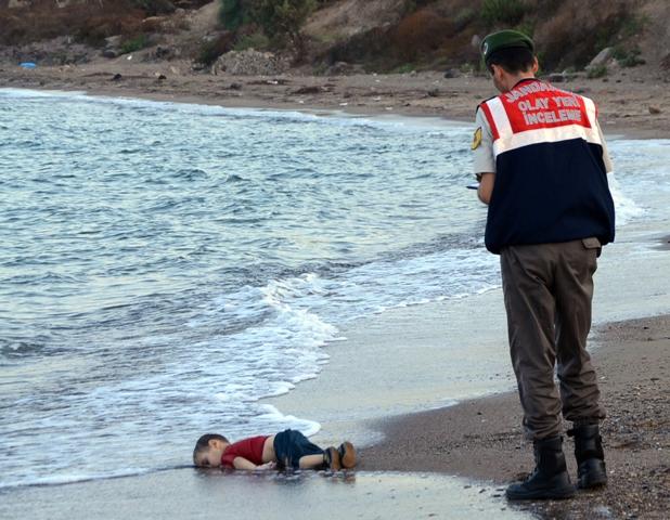Policajt stojí pri tele mŕtveho sýrskeho dieťaťa, ktoré vyplavilo more na pláž pri letovisku Bodrum, ktoré leží na pobreží Egejského mora na juhozápade Turecka