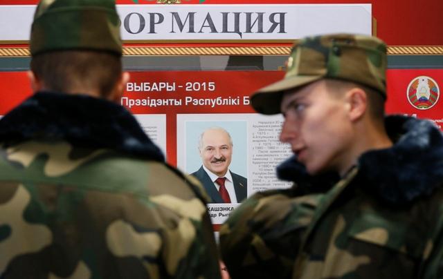 Na snímke bieloruskí armádni vojaci stoja pred portrétom bieloruského prezidenza Alexandra Lukašenka počas hlasovania v prezidentských voľbách v Minsku