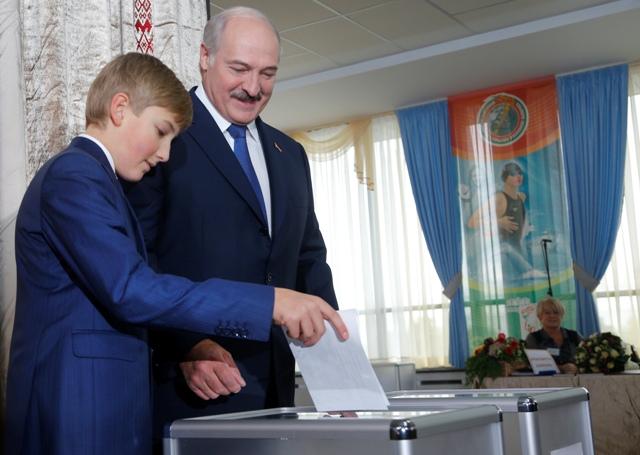 Na snímke bieloruský prezident Alexander Lukašenko a jeho najmladší syn Nikolaj počas hlasovania v prezidentských voľbách v Minsku