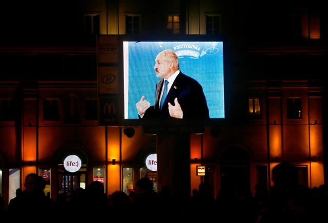 Bieloruský prezident Alexander Lukašenko na veľkoplošnej obrazovke sa vyjadruje k médiám po jeho hlasovaní v prezidentských voľbách v Minsku