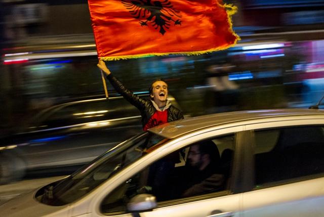 Kosovský Albánec máva albánskou vlajkou a oslavuje historicky prvý postup albánskej futbalovej reprezentácie na európsky šampionát v kosovskej metropole Priština