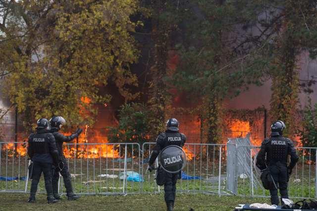 Slovinskí policajti sledujú plamene a dym v tábore pre migrantov v Brezici neďaleko slovinsko-chorvátskych hraníc