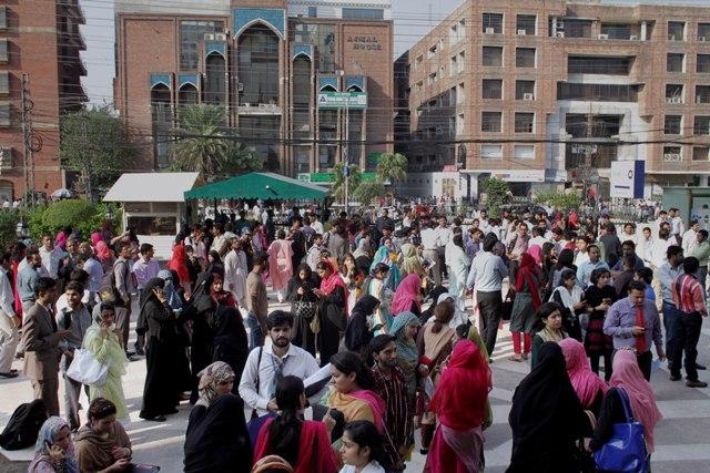 Ľudia stoja pred svojimi úradmi pri evakuácii po otrasoch počas zemetrasenia v pakistanskom Laháur