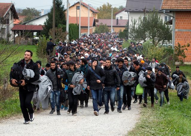 Na snímke veľká skupina migrantov kráča cez ulicu v chorvátskej obci Ključ Brdovečki neďaleko slovinských hraníc