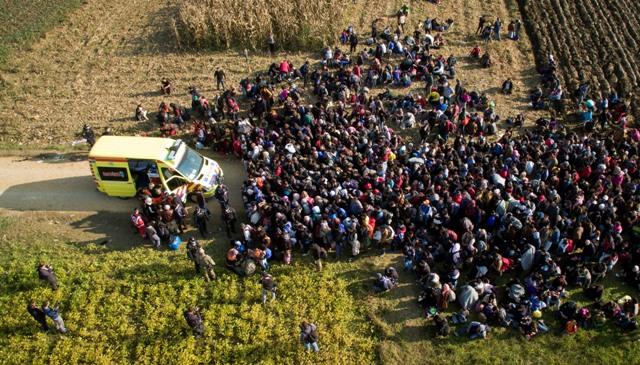 Na leteckej snímke migranti sú obklopení okolo sanitky po prekročení chorvátskych hraníc v slovinskej obci Rigonce