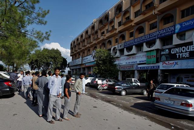 Ľudia stoja pred svojimi úradmi pri evakuácii po otrasoch počas zemetrasenia v pakistanskom Islamabade