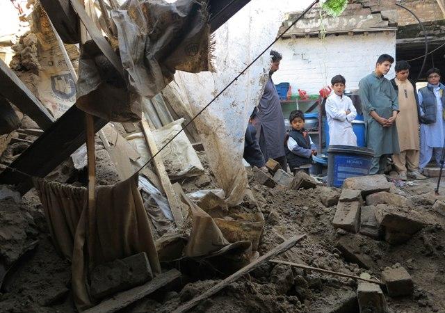 Ľudia sa pozerajú na dom zničený po otrasoch počas masívneho zemetrasenia v pakistanskom meste Mingora