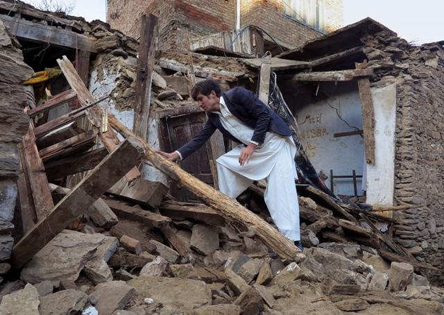 Pakistanec skúma dom zničený po otrasoch počas masívneho zemetrasenia v pakistanskom meste Mingora