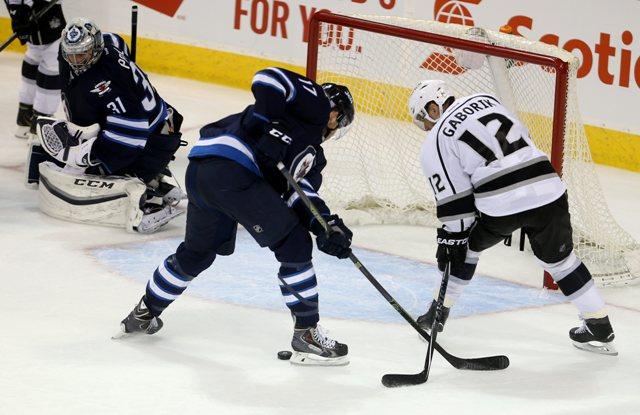 Hráč Winnipegu Jets Adam Lowry (17) zastavuje Slováka Mariána Gáboríka z Los Angeles Kings v hokejovom zápase zámorskej NHL vo Winnipegu
