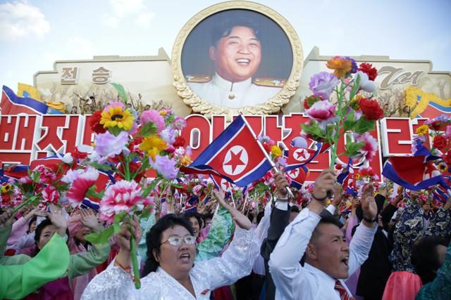 Na snímke ľudia mávajú vlajkami pred fotografiou zosnulého lídra  Kim Ir-sena počas vojenskej prehliadky v rámci 70. výročia založenia vládnucej Kórejskej strany práce 10. októbra 2015 v Pchjongjangu