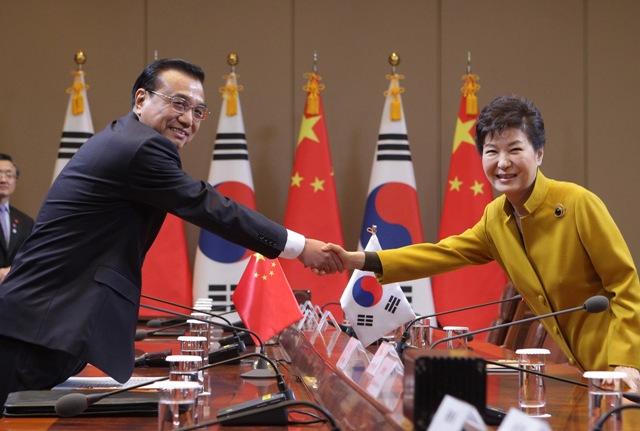 Na snímke juhokórejská prezidentka  Pak Kun-hje a čínsky premiér Li Kche-čchiang si podávajú ruky počas stretnutia pred bilaterálnym rokovaním v prezidentskom paláci v Soule