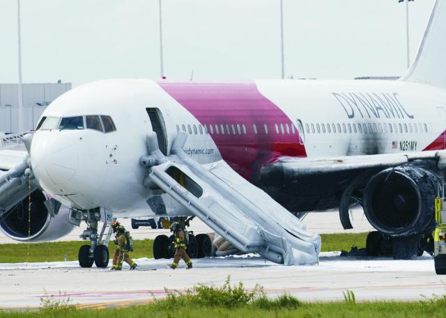 Pasažieri a členovia posádky sa evakuovali z horiaceho Boeningu 767 ( na snímke)pomocou núdzových šmýkačiek