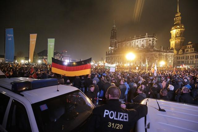 Na snímke nemecký policajt stojí pred demonštrantmi počas demonštrácie skupiny PEGIDA proti islamizácii Západu pred katedrálou v Drážďanoch