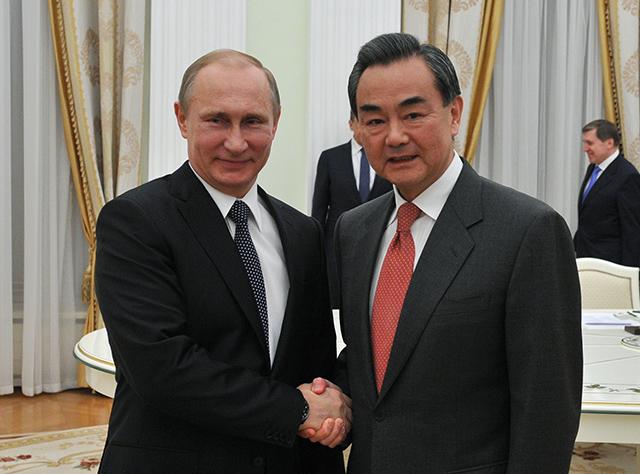 Na snímke vľavo ruský prezident Vladimir Putin a vpravo čínsky minister zahraničných vecí Wang I