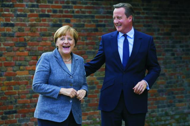 Britský premiér David Cameron sa usmieva počas stretnutia s nemeckou kancelárkou Angelou Merkelovou neďaleko Ellesboroughu 9. októbra 2015