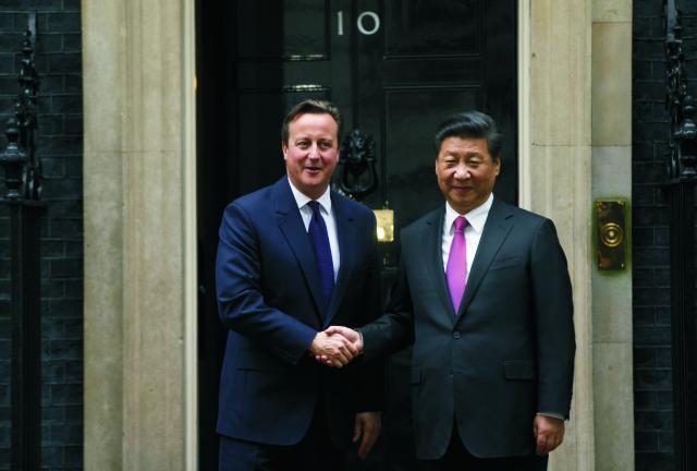 Britský premiér David Cameron (vľavo) si podáva ruku s čínskym prezidentom Si Ťin-pchingom počas ich stretnutia na Downing Street 10 v Londýne 21. októbra 2015. Si je na štvordňovej štátnej návšteve Británie