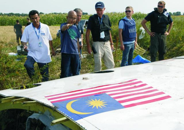 Na archívnej snímke malajzijskí leteckí vyšetrovatelia a pozorovatelia OBSE skúmajú časti trosiek z civilného lietadla spoločnosti Malaysian Airlines 23. júla 2014 pri dedine Petropavlivka na východe Ukrajiny.  Malajzijský Boeing 777 sa 17. júla 2014 zrútil na východe Ukrajiny v pohraničnom území kontrolovanom proruskými silami. O život prišlo všetkých 298 ľudí na palube