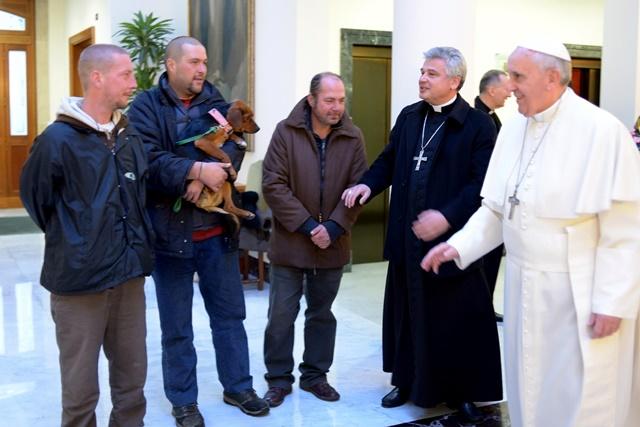 Na snímke z roku 2013 pápež František (vpravo) v sprievode pápežského almužníka Mons. Konrada Krajewského (druhý sprava) prijíma štyroch bezdomovcov