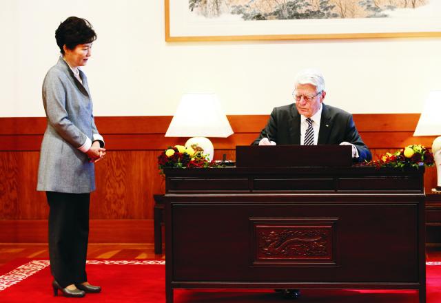 Nemecký prezident Joachim Gauck sa podpisuje do knihy návštev v prezidentskom paláci v Soule 12. októbra 2015. Vľavo stojí  juhokórejská prezidentka Pak Kun-hje. Gauck je na štvordňovej oficiálnej návšteve Južnej Kórey. Jej cieľom je prehĺbiť spolupráci medzi oboma krajinami