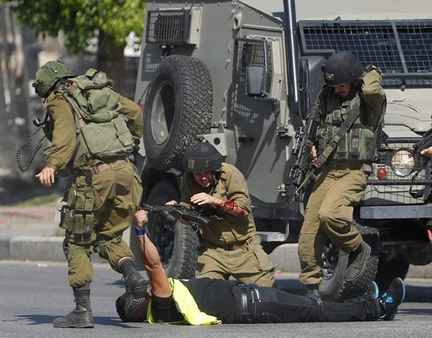 Na snímke izraelský vojak pomáha svojmu pobodanému kolegovi