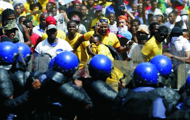 Juhoafrickí študenti hádžu kamene na príslušníkov poriadkových síl počas protestu proti zavedeniu školného pred jednotnou budovou v Pretórii