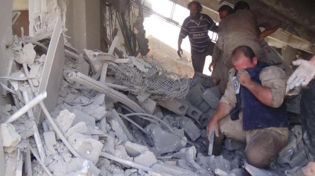 Na snímke zverejnenej na účte sýrskej civilnej obrany známej pod názvom Biele helmy dobrovoľník prehľadáva trosky po ruských náletoch v Talbisehu, v sýrskej provincii Homs