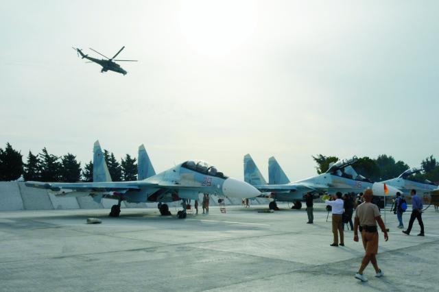 Novinári filmujú ruské stíhačky Su-30 na sýrskej leteckej základni Hemeimeem 22. októbra 2015. Od skorého rána ruské bojové stíhačky vzlietli z tejto základne v západnej Sýrii na vojenskú misiu