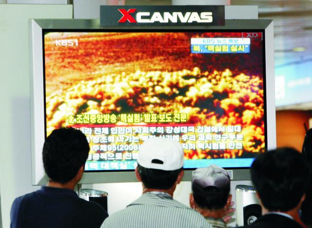 Kórejčania pozerajú archívny televízny záznam z predchádzjúceho  jadrového testu