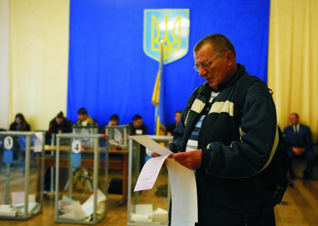Volič si kontroluje volebné lístky vo volebnej miestnosti v Kyjeve počas regionálnych volieb 25. októbra 2015. Na Ukrajine sa začali dnes voľby do miestnych samospráv. Ukrajinci si zvolia zástupcov do 10.778 regionálnych, mestských a okresných rád prostredníctvom pomerného volebného systému