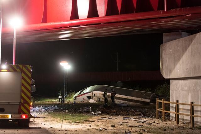 Na snímke záchranári stoja neďaleko vykoľajeného rýchlovlaku TGV vo francúzskom Eckerwersheime